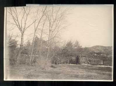 Photograph of a Hut and a Wooden Fence. Photograph.
